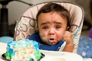 Unhappy baby eating cake